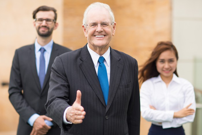 An older man in a suit smiles and gives a thumbs-up, with two younger people standing behind him.